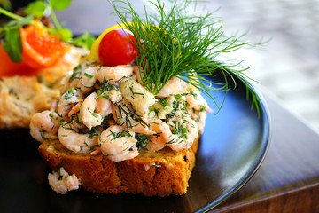 Scandinavian Smorrebrod open-faced sandwich with cold shrimp in Denmark