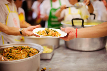 Hands of volunteers serves free food to the poor and needy in the city