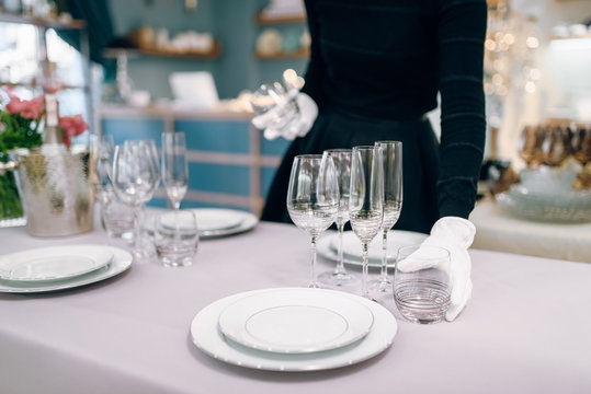 Waitress in gloves puts tableware, table setting