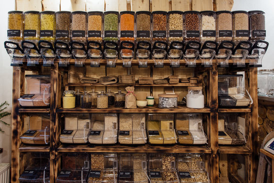 Front view of variety of seeds and nuts displayed in grocery store. Zero waste shopping - shelf with glass jars full of dry food in organic shop.