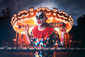Crazy clown with baseball bat in amusement park