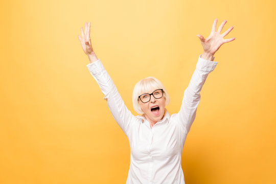 I'm winner! Portrait of a cheerful senior woman gesturing victory isolated over yellow background.
