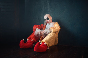 Tired bloody clown with bat sitting on the floor