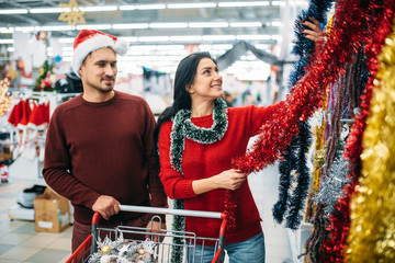 Young couple choosing holiday fluffy garland