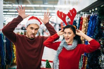 Playful couple choosing christmas decorations