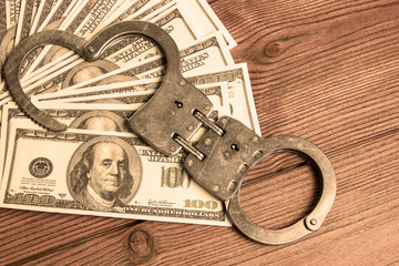 iron handcuffs to detain criminals, us dollar bills on the background of a wooden table. corruption.
