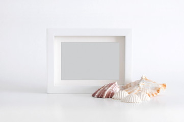 White empty photo frame with light grey color inside and sea shells, on white background. Clipping path inside the frame