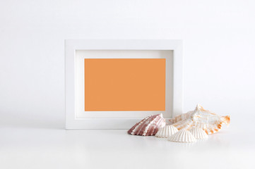 White empty photo frame with orange color inside and sea shells, on white background. Clipping path inside the frame