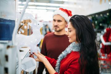 Couple looks on glass deer in supermarket