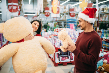 Young couple choosing plush toys in supermarket