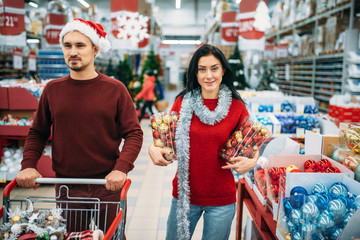 Young couple chose a lot of Christmas toys in shop