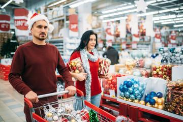Young couple buying a lot of Christmas decorations