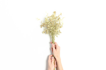 Woman hold in hands a bouquet of dry oats