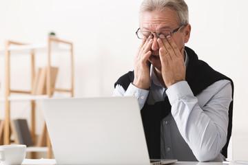 Hard day. Elderly man feeling tired, working on laptop