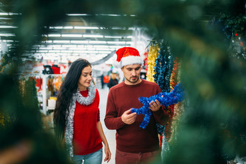 Couple looks on holiday decorations in supermarket
