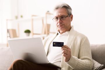 Mature man shopping online on laptop, using credit card