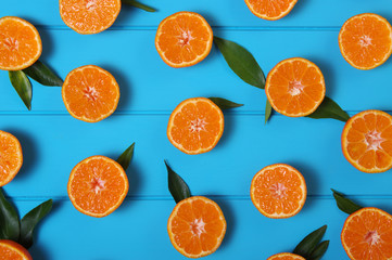 tangerines with green leaves on turquoise  background.