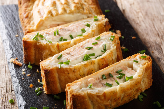 Sliced puff pastry pie stuffed with salmon and cheese close-up. horizontal
