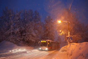 A bus drives on the road during heavy snowfall in Reitdorf