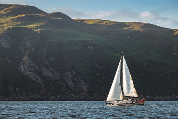 Touristic yacht sailing next to the Northern Ireland steep rocks. Green covered heels, shoreline. Outdoor activity. Perfect background for the creating of various kinds of collages and illustrations.