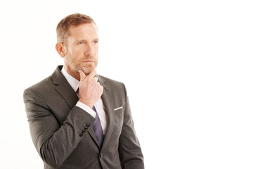 Businessman deep in thought. Man standing against white background
