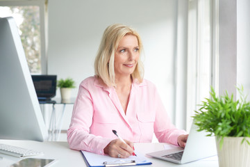 Senior professional woman sitting at office desk and working