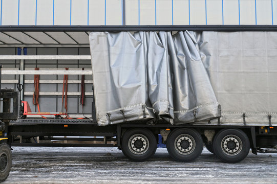 A semi-trailer with an exposed tarpaulin during unloading. Transport and unloading.