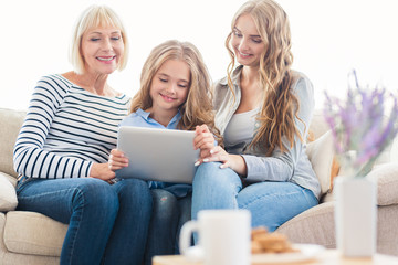 Family with tablet computer at home on sofa