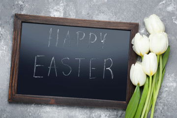 Inscription Happy Easter on wooden frame with white tulips