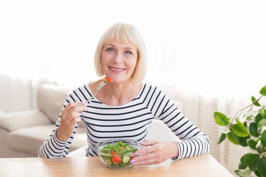 Happy senior lady eating fresh salad at home