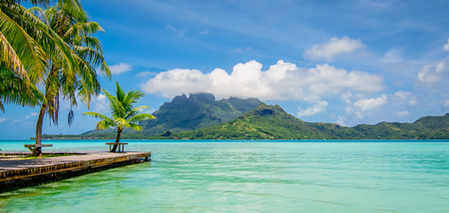 Beautiful Island with lagoon, palm trees and mount Otemanu in the background. Panoramic view of Bora Bora, French Polynesia.