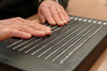 A man demonstrates the Canute 360, a multi-line braille e-reader developed by Bristol Braille Technologies that the company describes as a 'Kindle for the blind' in Reading