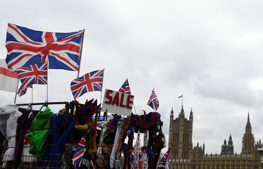 Union Jack flags and a sale sign are seen outside the Houses of Parliament in London