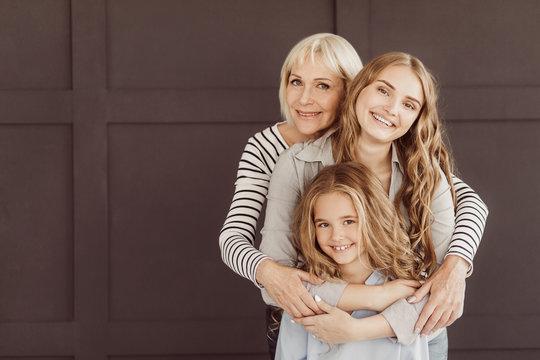 Three generations of happy women looking at camera