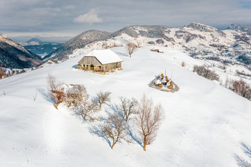 Traditional peasant house covered with snow in the Pestera Village near Moeciu and Bran Romania