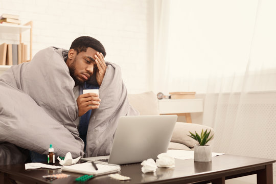 Sick african-american man working on laptop at home