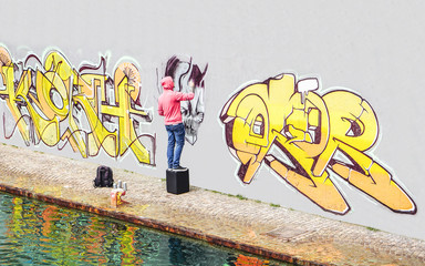 Street graffiti artist painting with a color spray can a graffiti on the wall in the city - Concept...