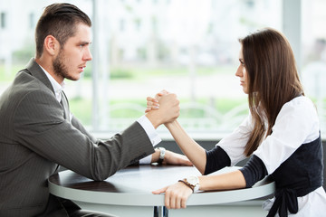 business and office concept - businesswoman and businessman arm wrestling during meeting in office.