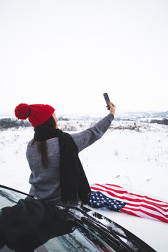 young adult woman traveler sitting on the hood of the suv car with usa flag taking picture on her phone