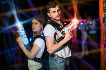 Man and woman back to back in laser beams