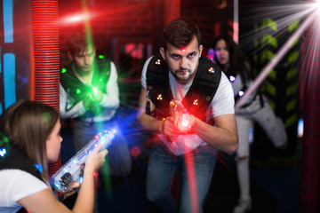 Excited guy laser tag player in bright beams
