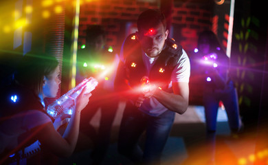 Emotional guy playing laser tag in colorful beams