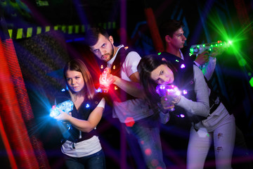 Young people playing laser tag in bright beams