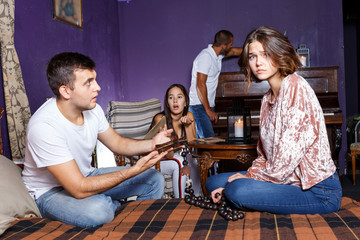 Young people with wooden rosary in escape room