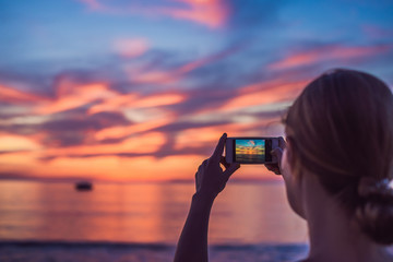 Young asia woman selfie with mobile phone on a beach at sunset in summer, Phuket, Thailand