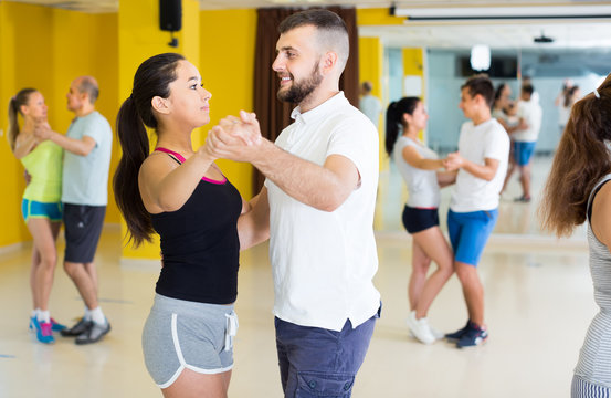 Smiling dancing couples learning salsa