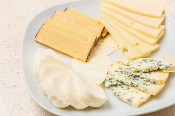 Assorted cheese sliced cheese on white plate