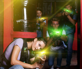 Young woman with laser guns  took aim during laser tag game