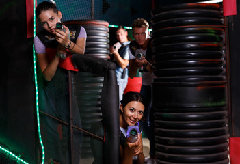 Friends playing laser tag  game with laser guns together in dark labyrinth