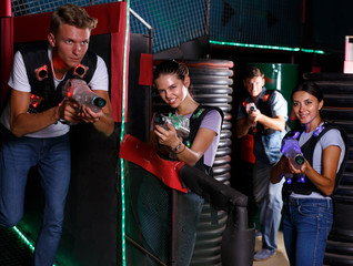 Young men and girl in waistcoats with laser guns playing laser tag  game